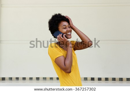 Portrait of young black woman talking on mobile phone and smiling with her hand on head - stock photo