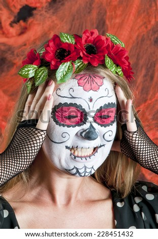 Portrait of young blond girl in black dress with Calavera Mexicana makeup mask with emotions of horror on her face - stock photo
