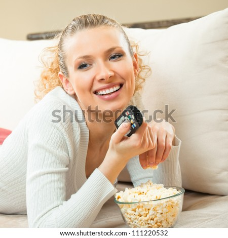 Portrait of young blond happy smiling woman watching TV at home - stock photo