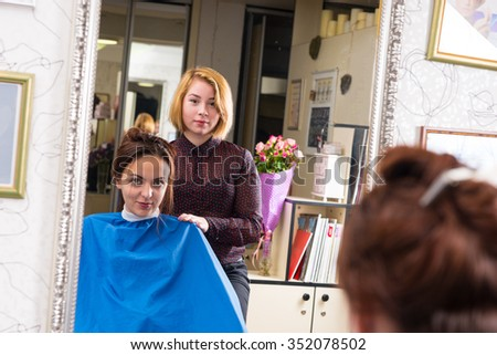 Portrait of Young Blond Stylist Standing Behind Young Brunette Female Client Wearing Blue Smock and Sitting in Chair in Salon - Reflection in Large Mirror