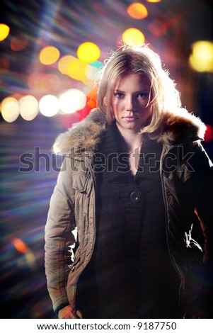 Portrait of young blond woman in parka at night. - stock photo
