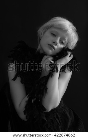 Portrait of young blond woman posing with feathers on black background -  Black and White Photography - stock photo
