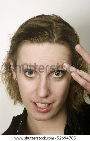 Portrait of young blond woman touches the eyebrow - stock photo