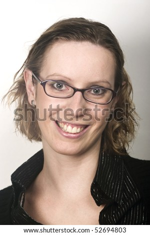 Portrait of young blond woman with glasses smiling into camera - stock photo