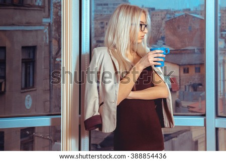 Portrait of young blonde business woman with cup of tea near the large window with city views. Business woman drinks tea. City views behind the window in the office. Business concept. - stock photo