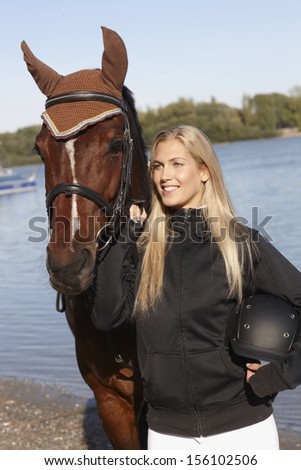 Portrait of young blonde female rider and horse at riverside. - stock photo