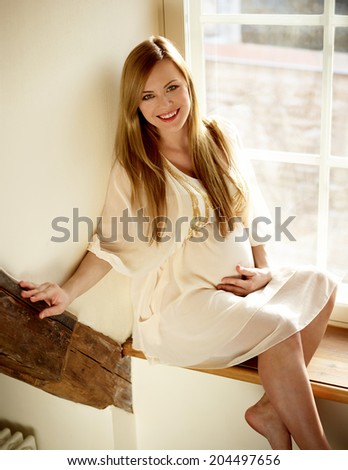 Portrait Of Young Blonde Pregnant Woman Sitting Near Window