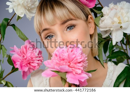 Portrait of young blonde pretty girl among flowers looking at camera over grey background.