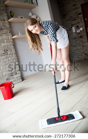 Portrait Of Young Blonde Woman Mopping Floor At Home - stock photo