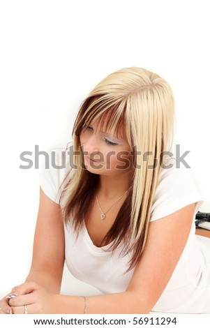 Portrait of young blonde woman relaxing, studio shot
