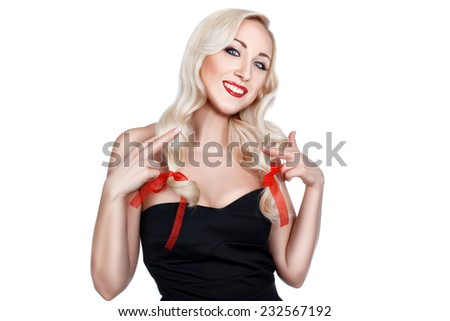 Portrait of young blonde woman with long curly hair, holding flirtatiously strands. - stock photo