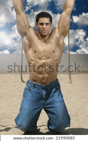 Portrait of young bodybuilder hanging on beach with bright blue sky - stock photo