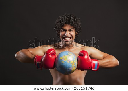 Portrait of young boxer breaking globe - stock photo