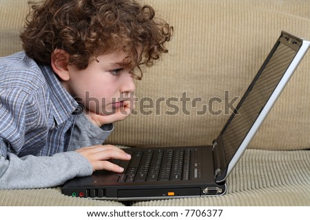 Portrait of young boy at the laptop - stock photo