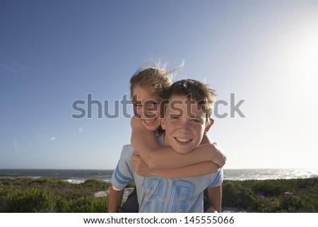 Portrait of young boy giving sister piggyback ride with ocean in background - stock photo