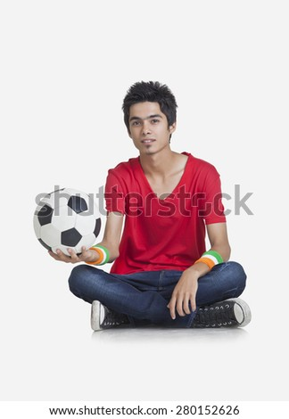 Portrait of young boy in casual wear holding soccer ball over white background - stock photo
