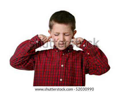 Portrait of young boy in plaid shirt covering his ears, studio shot - stock photo