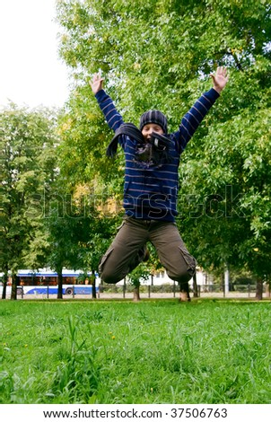 portrait of young boy jumping in the park - stock photo