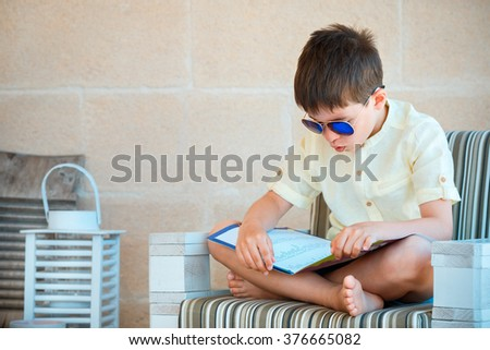 Portrait of young boy reading for elementary school a book on outdoor terrace - stock photo