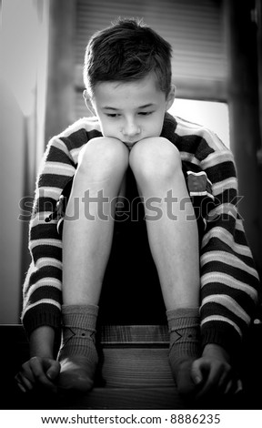 Portrait of young boy sitting sadly - stock photo