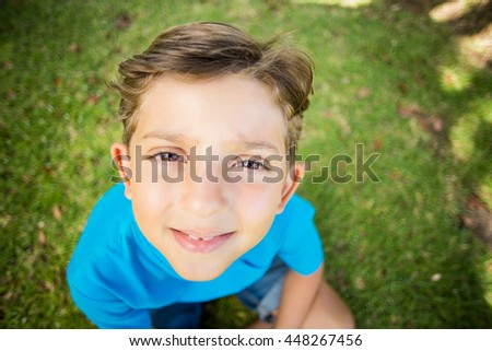 Portrait of young boy smiling at camera in park - stock photo