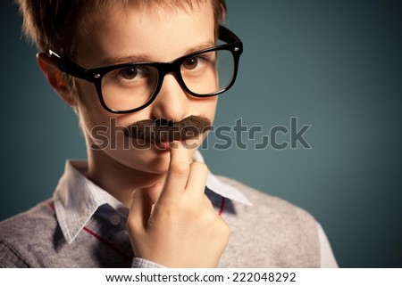 Portrait of young boy with fake moustache and glasses. - stock photo