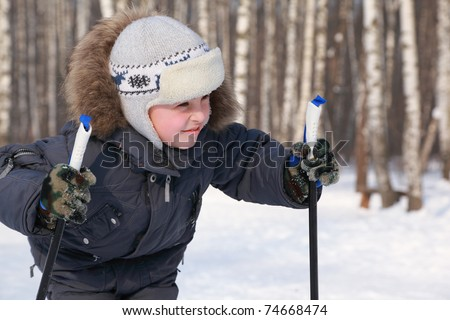 Portrait of young boy with ski poles looking to side inside winter forest at sunny day - stock photo