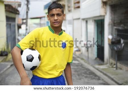 Portrait of young Brazilian football player holding soccer ball on neighborhood street - stock photo