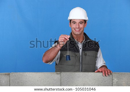 portrait of young bricklayer posing near unfinished concrete wall holding bell - stock photo