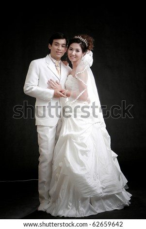 Portrait of young bride and groom standing in black background - stock photo