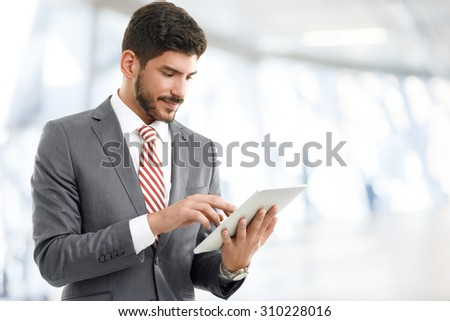 Portrait of young broker standing at office while holding digital tablet in his hands. Young businessman touching digital tablet and checking financial data.  - stock photo