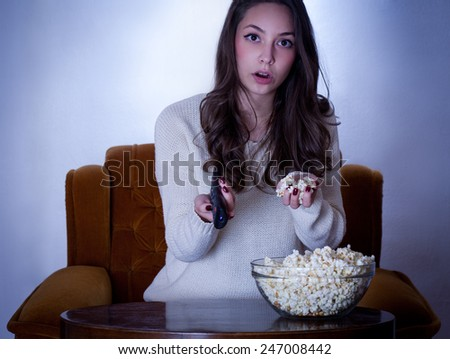 Portrait of young brunette in front of the television. - stock photo