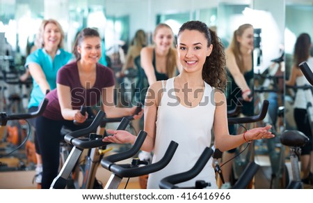 Portrait of young brunette smiling in exercise bikes class  - stock photo