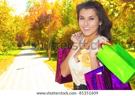 Portrait of young  brunette smiling woman holding packets at  green park - stock photo