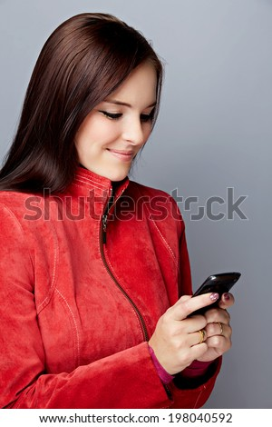 Portrait of young brunette woman in red leather jacket with a smartphone  - stock photo