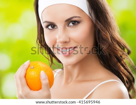 Portrait of young brunette woman with orange, outdoors. Healthy lifestyle, beauty and dieting concept. - stock photo