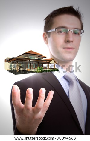 Portrait of young business man holding house - stock photo