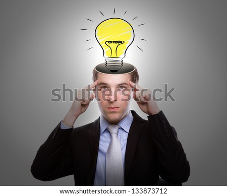 Portrait of young business man thinking with light bulb out from head - stock photo