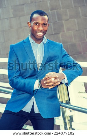 Portrait of Young Business Man. Wearing a blue blazer, black pants,, short haircut, bracelets, finger ring, a young black guy is standing against metal fences by the wall, smiling, looking at you.  - stock photo