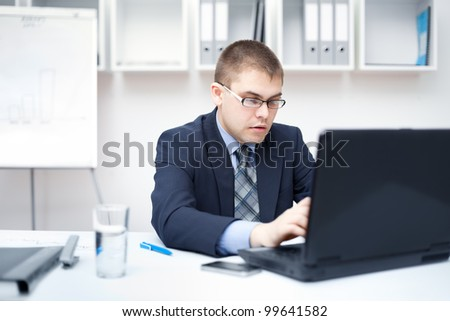 Portrait of young business man working on a laptop at office