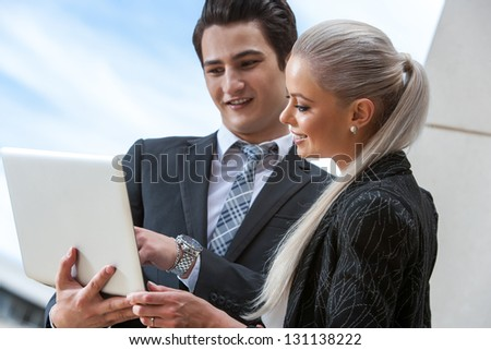 Portrait of young business partners reviewing information on laptop outdoors. - stock photo
