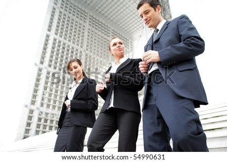 Portrait of young business people coming down stairs - stock photo