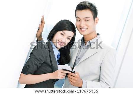Portrait of young business travelers with passport and tickets looking at camera in airport - stock photo