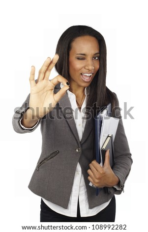 Portrait of young business woman doing Ok sign and winking - stock photo