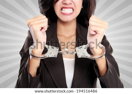 portrait of young business woman in handcuffs - stock photo