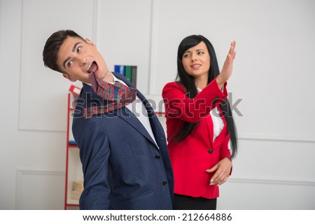 Portrait of young business woman in red jacket  giving a slap in the face to her flirting colleague in office, relationship at work concept - stock photo