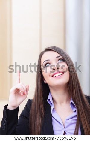 Portrait of young business woman pointing up at copyspace - stock photo