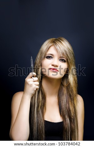 Portrait of young business woman pointing with pen in hand to empty advertising copy space in a place you ad here concept, on dark background - stock photo