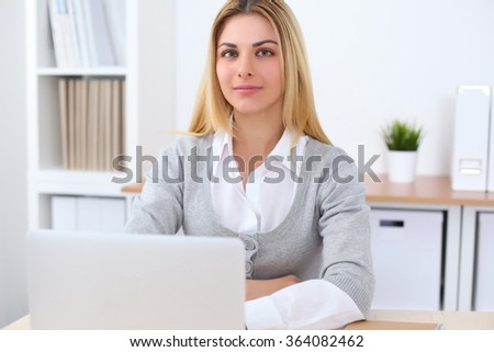 Portrait of young business woman sitting at the desk on office background