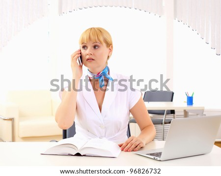 Portrait of young business woman sitting at the table. - stock photo